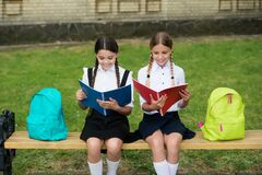Little kids in school uniforms read library books sitting on bench outdoors, reading