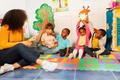 Little kids show sun rainbow cards in nursery stock photography