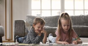 Little kids siblings drawing together in paper album.