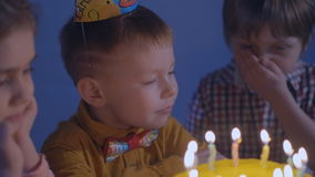 Little kids sit at red table with cake and blow in multicolor party blowers at birthday party. Happy group of children. Little kids sit at red table with cake stock video