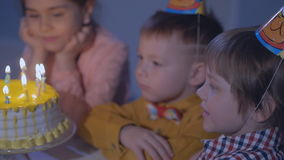 Little kids sit at red table with cake and blow in multicolor party blowers at birthday party. Inscription Happy Birthday on wall stock video
