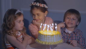 Little kids sit at red table with cake. Happy group of children at birthday party. Little kids sit at red table with cake and blow in multicolor party blowers stock video footage