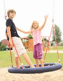 Little kids standing on a net swing. Hairy little girl and boy standing and swinging on a net swing made from ropes with kids playground behind Royalty Free Stock Images