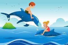 Little Kids Swimming with Dolphins in the Ocean Royalty Free Stock Images