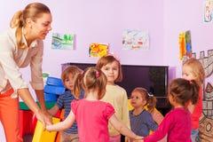 Little kids and teacher roundelay around one girl Stock Photo