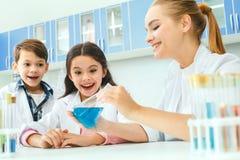 Little kids with teacher in school laboratory result stock photo