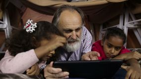 Little kids teaching grandfather to use tablet stock video