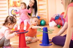 Little kids with their mothers in kindergarten gym royalty free stock image