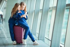 Little adorable girls in airport near big window. Little kids together in airport waiting for boarding Stock Photos