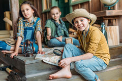 Little kids travelers sitting together with map on porch. Adorable little kids travelers sitting together with map on porch Royalty Free Stock Photos