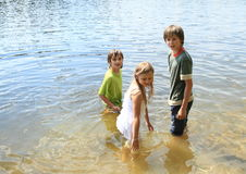 Little kids in water. Little kids - girl and two boys in clothes going into the water and soaking wet Stock Photo