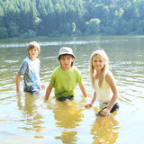 Little kids in water. Little kids - girl and two boys in clothes having fun in water and soaking wet royalty free stock photo