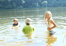 Little kids in water. Little kids - girl and two boys in wet clothes swimming and having fun in water stock images