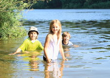 Little kids in water. Little kids - girl and two boys in wet clothes swimming and having fun in water stock photo