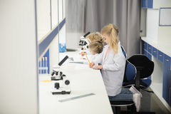 Little kids wearing lab coats and studying. In science laboratory royalty free stock photo