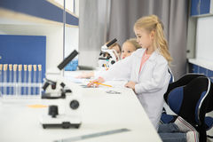 Little kids wearing lab coats and studying. In science laboratory royalty free stock photography