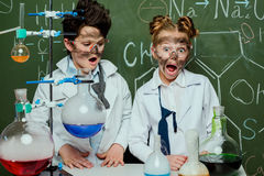 Little kids in white coats with chalkboard behind in science laboratory. Scientists kids team concept stock images