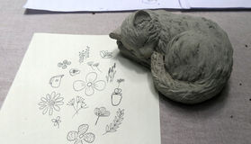 Little kitten sculpture and drawing flowers. Little cat sculpture and garden flower pencil drawing on white paper artist creative and design in the park royalty free stock images