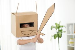 Little knight. Little boy playing in carbord helmet with sword in his hands Royalty Free Stock Images