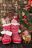 Little knitted boots with presents. Little red knitted boots with presents and treats for christmas Royalty Free Stock Photography