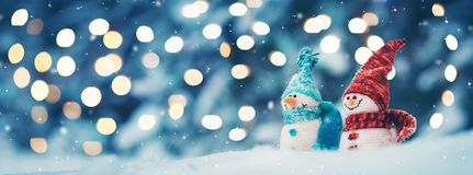 Little snowmans on soft snow on blue background royalty free stock photos