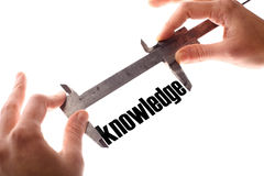 Little knowledge. Color horizontal shot of two hands holding a caliper measuring the word knowledge Stock Photos