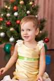 Little lady in gold at the christmas tree Royalty Free Stock Photography