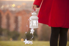 Little lantern with magic illumination hold by a woman in a red. Detail of a little lantern with magic illumination hold by a woman in a red coat in the park at royalty free stock photo