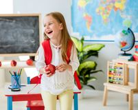 Little laughing blond girl holding an apple in the school classroom stock images