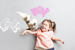 Little laughing cute girl fighting with toy cat. Comic scene Royalty Free Stock Image