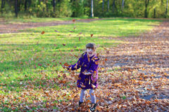 Little laughing girl in coat throws up leaves Royalty Free Stock Photography