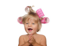 Little laughing girl with hair curlers Royalty Free Stock Images