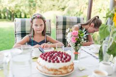 Little laughing girl at her birthday party on the garden terrace sitting at the table with a birthday cake. Authentic family life royalty free stock image