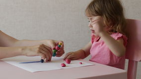 Little laughing girl and mom play with plasticine at home. Portrait little girl play with plasticine. A happy family stock video