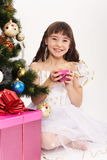 Little laughing girl opening christmas present. Under a Christmas tree Royalty Free Stock Images