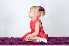 Little laughing girl is sitting on a purple carpet in the studio Stock Image