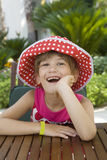 Little laughing girl in spot Panama Royalty Free Stock Images