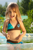 Little laughing girl in swimming pool. Summer and sunshine. Little beautiful laughing loudly girl in outdoor small swimming pool royalty free stock images