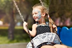 Little laughing girl swinging on a swing royalty free stock images