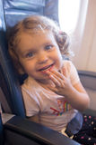 Little laughing girl is traveling by plane. Stock Photos