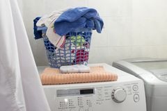 Clean laundry basket over the washing machine. stock image