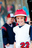 Little league baseball boy in dugout. Little league baseball boy with helmet in dugout smiling Royalty Free Stock Photography