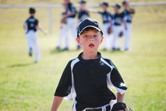 Little league baseball boy running on field. Youth baseball boy with team in background Stock Photo
