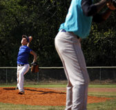 Little league baseball pitcher. A young boy  is pitching right handed  to a batter, pitcher is in motion, ball still in hand but about to release.  View is from Stock Image