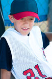 LIttle league baseball player in dugout Royalty Free Stock Images