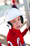 Little league baseball player in dugout Stock Photography