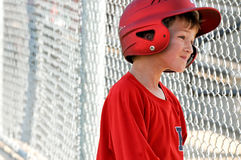 Little league baseball player in dugout Royalty Free Stock Image