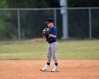 Young boy fielding and throwing the ball in a baseball game