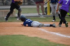 Young boy playing Little League Baseball. Little league baseball player during a YMCA baseball game. Cute boy in blue and grey uniform royalty free stock photo