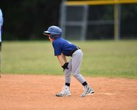 Young boy playing Little League Baseball. Little league baseball player during a YMCA baseball game. Cute boy in blue and grey uniform stock photography